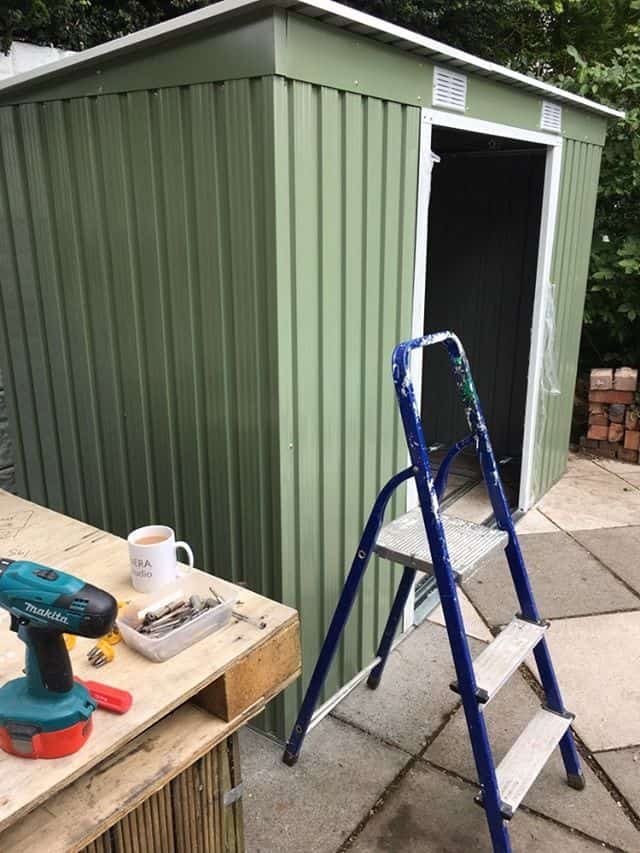 metal shed built on paving stones with a step ladder and a pallet with coffee mug and drill on top