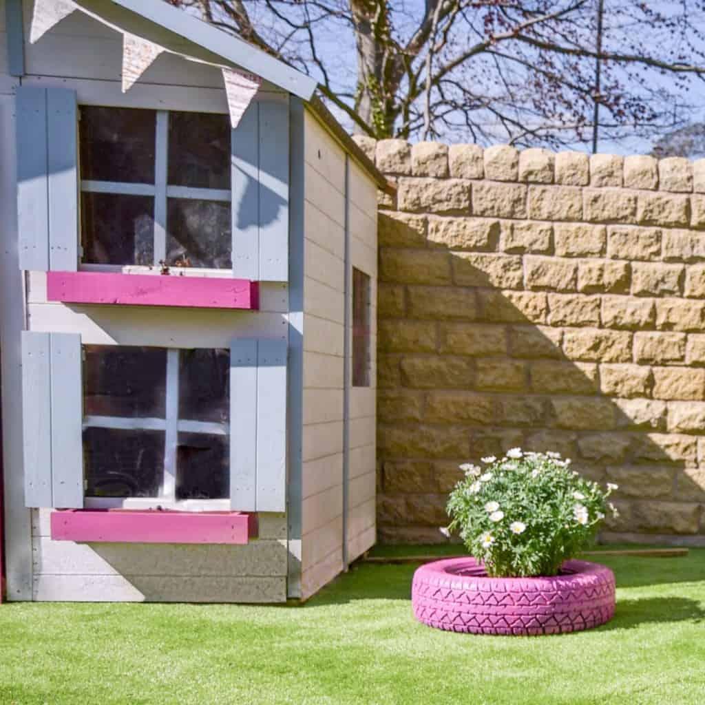 Pink peardrop playhouse in a cosy garden
