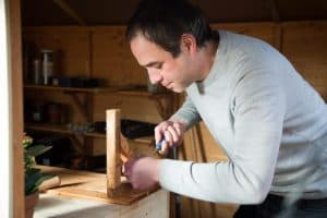 A man leaning over a table leg on a benchtop does carpentry