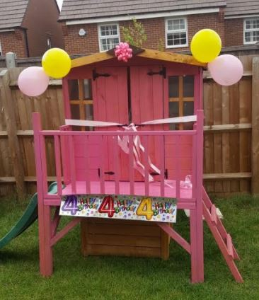 Bunny tower playhouse painted pink in a garden