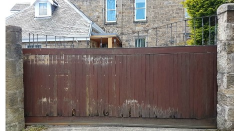Wooden double driveway gates with rot in front of a large house