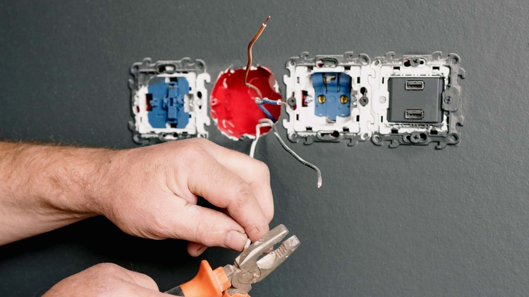 Electrician's hands holding pliers attaching wires to wall sockets on grey wall