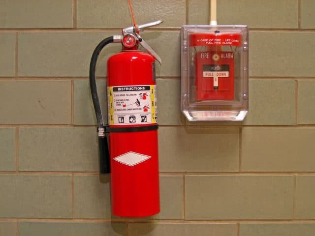 Fire Extinguisher and Alarm on Green Cinderblock Background