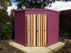 Pent roof shed in a corner on slabs painted purple with multi-coloured striped painted on locked door