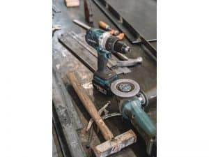 Makita drill and axle grinder on sheet metal with a wooden handled hammer