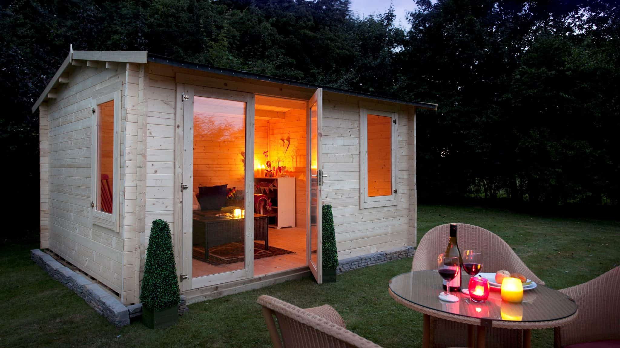 wooden shed summerhouse at the end of a garden in front of a small table with drinks and lights on it with its door open and lit up inside