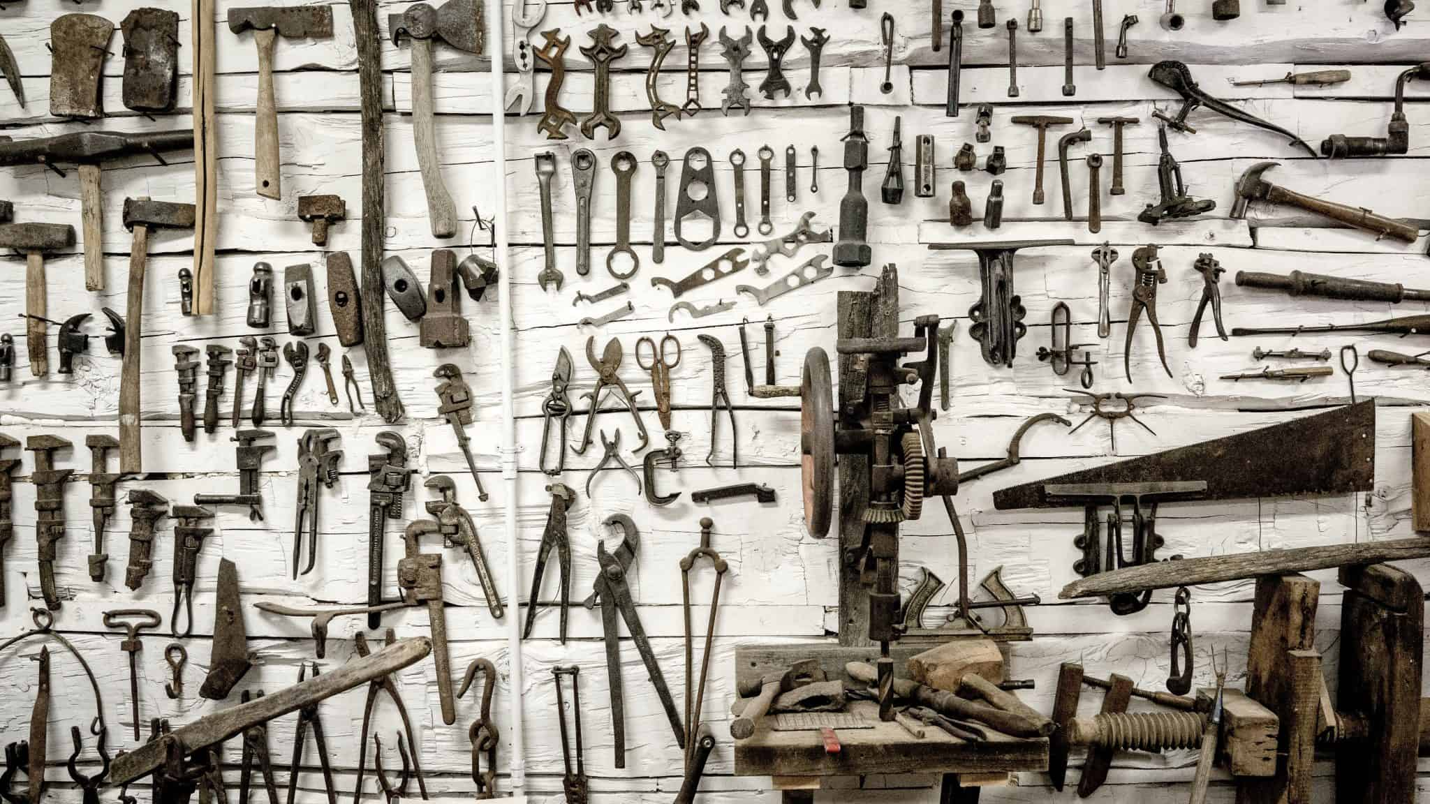 wall filled with various tools hung from it including axes and spanners