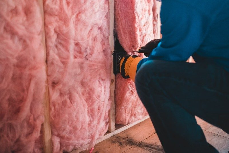 pink wall insulation being fitted by crouching person