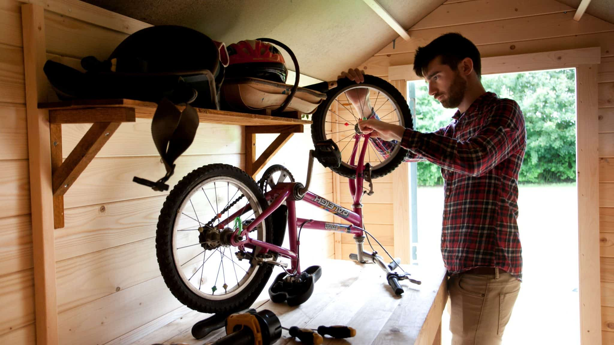 open shed with man inside putting upturned bike back on shelving