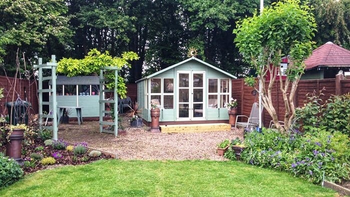 Garden shed with front windows at the end of a garden on a gravel patch