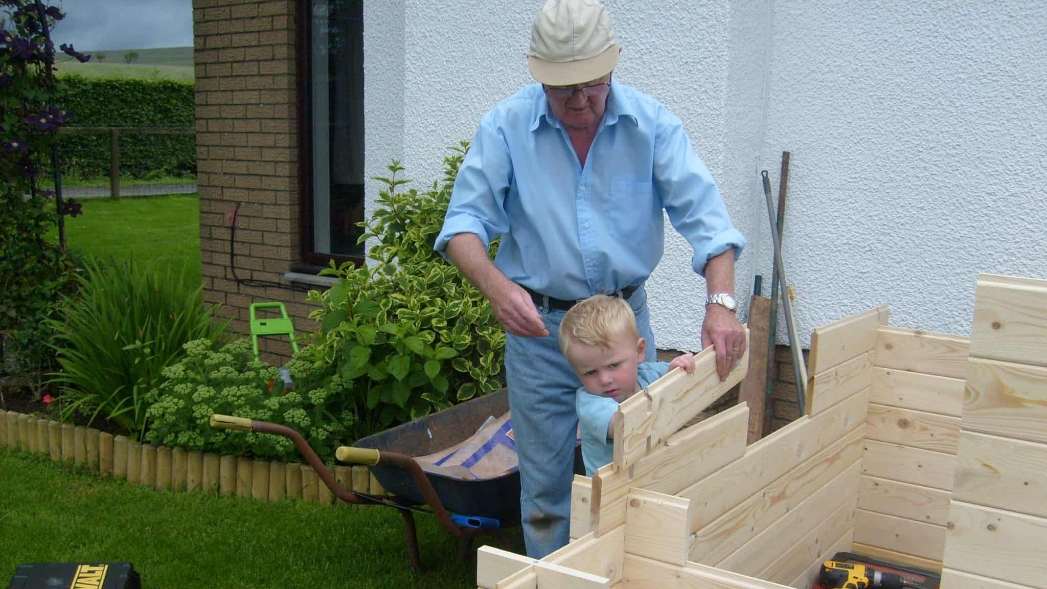 older man in a blue shirt and cap helping a young blonde child build a timber shed wall in the garden